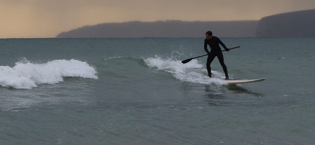 About Paddles Up Training. Image of person SUP surfing on sea