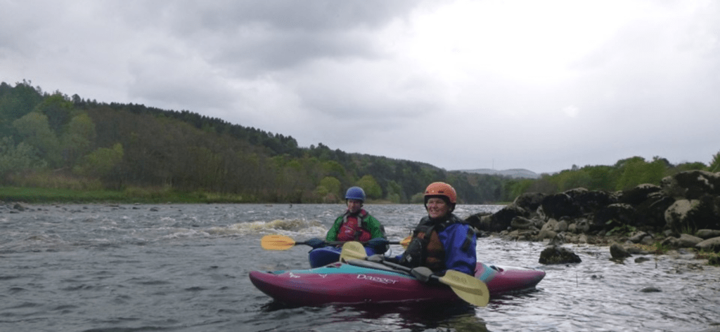 2 white water kayakers resting in an eddy